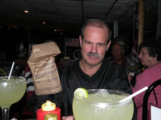"Here is R. B. at the Margaritagrille using the unique ""paper bag"" menu as a hand puppet. He is feeling his Margarita."