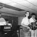 This is an unusual photo. There I (Buzz) am at the organ, and Ronnie is on the drums. I see three guitars in the front line, but No Sax. Where is Rodney? Who is playing the third guitar?